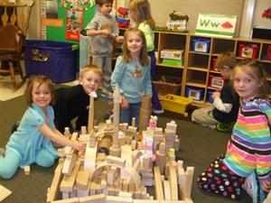 Preschoolers playing with blocks and stopping to smile