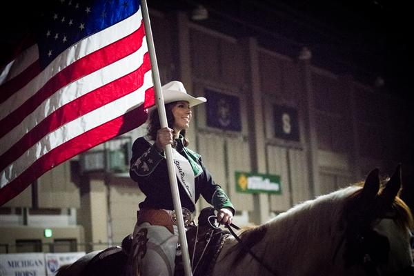 Claire Daugherty on horseback with American Flag